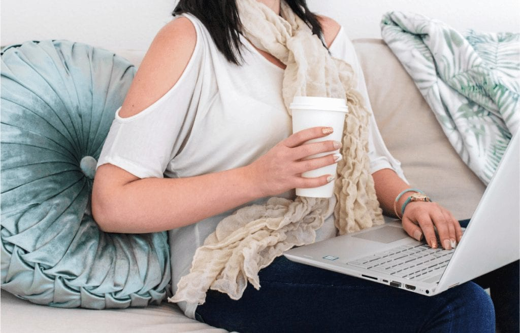 female holding coffee on laptop